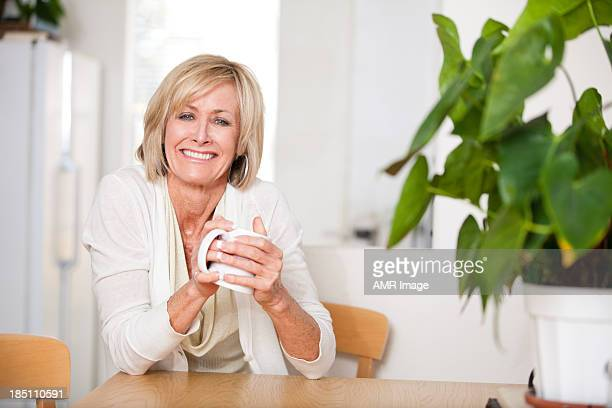 Cheerful middle aged woman enjoying hot tea