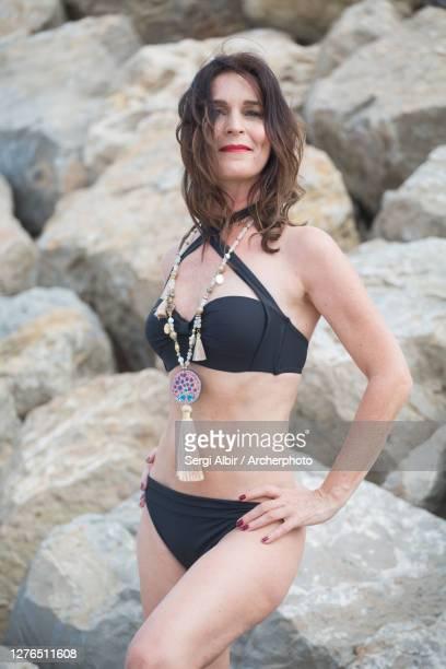 cheerful middle-aged woman in a black bikini in valencia beach - sergi albir fotografías e imágenes de stock