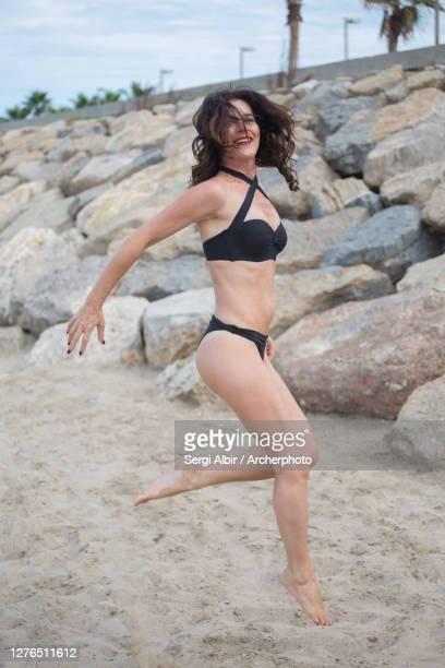 cheerful middle-aged woman jumping in a black bikini in valencia beach - sergi albir fotografías e imágenes de stock