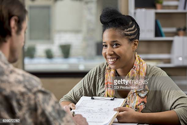 Cheerful military counselor assists veteran with paperwork
