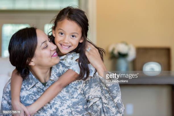 cheerful military mom is reunited with adorable daughter - army soldier stock pictures, royalty-free photos & images