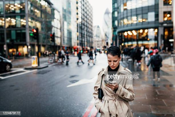 cheerful millennial woman using mobile app to find taxi or ridesharing car - northern european stock pictures, royalty-free photos & images