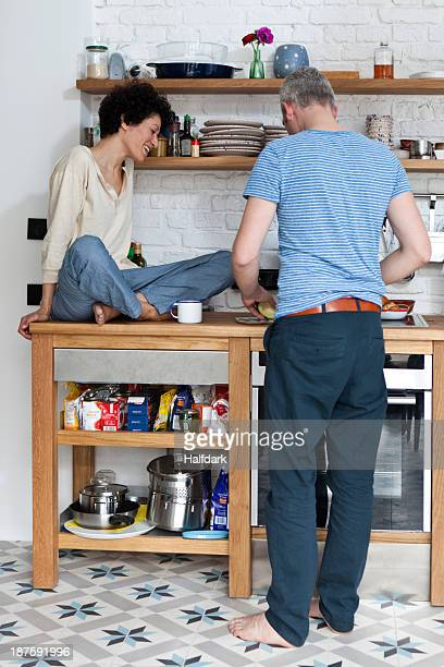 A cheerful mixed age couple preparing food in their kitchen