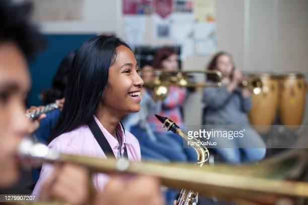 陽気な混合民族アジアの女の子とサックスバンドオーケストラクラス - ブラスバンド ストックフォトと画像