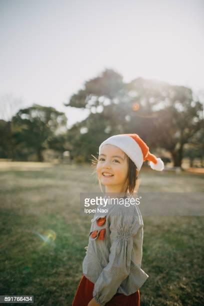 Cheerful mixed race little girl wearing santa claus hat
