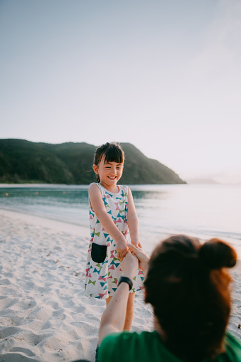 Cheerful mixed race preschool girl holding mother's hands on beach at sunset, Okinawa, Japan - gettyimageskorea