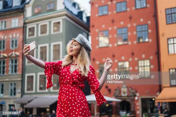 ガムラスタンの通りでセフリーを取る陽気な現代の女性 - 赤のドレス ストックフォトと画像