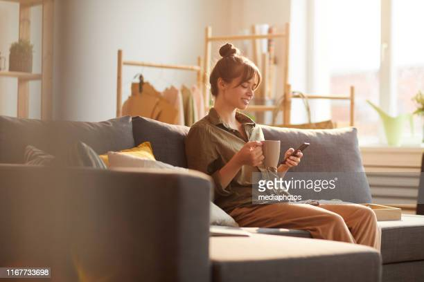 cheerful modern young woman with hair bun sitting on sofa and reading internet news over coffee - social media marketing stock pictures, royalty-free photos & images