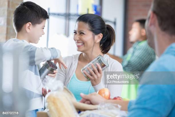Cheerful mom and son volunteer at a food bank