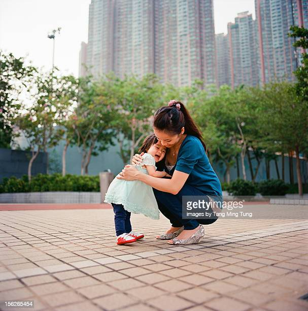 Cheerful mom & laughing baby hugging on playground