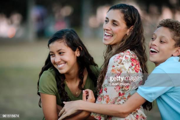 cheerful mother and children looking away at park - mexican mom stock photos and pictures