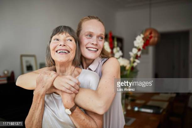 cheerful mother and daughter at home - happy mothers day mom stock-fotos und bilder