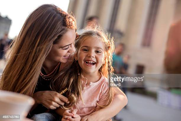 Cheerful mother and daughter having fun together in the city.