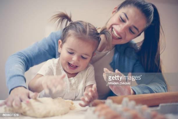 Vrolijke moeder en dochter op zoek op hand spelen met deeg voor cookie.