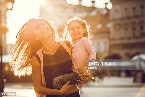 Cheerful mother and daughter running in the city at sunset.