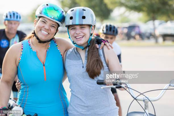 cheerful mother and daughter smile for camera before bike race - charity benefit stock photos and pictures