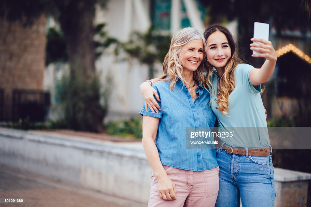 Cheerful mother and daughter taking selfies together in the city : Stock Photo