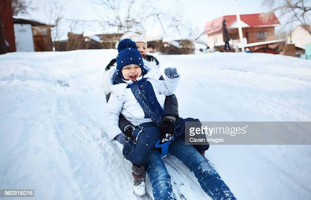 Cheerful mother and daughter tobogganing on snowy field
