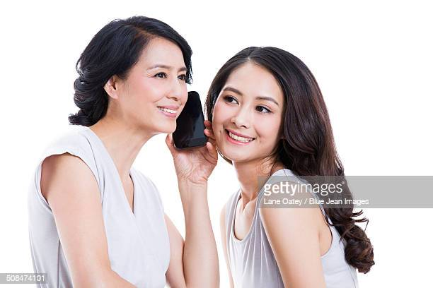 Cheerful mother and daughter with mobile phone