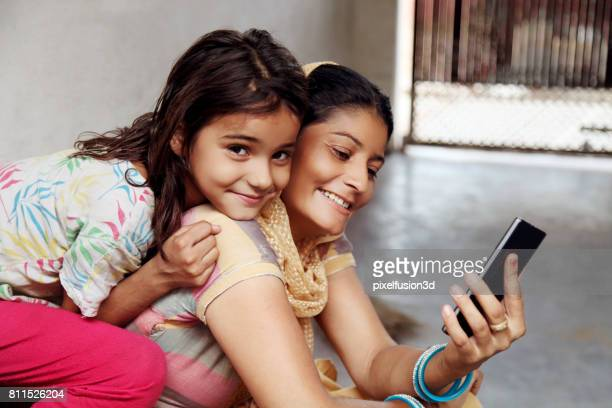 Cheerful  mother & daughter using mobile phone at home