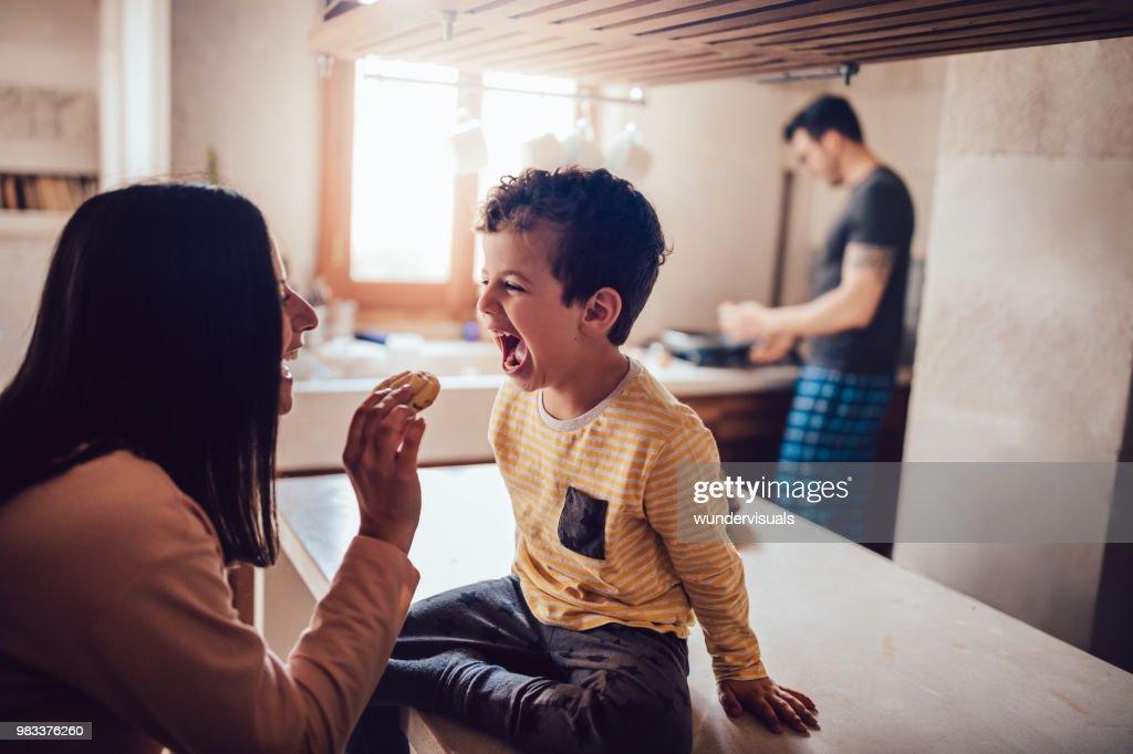 Fröhliche Mutter gibt kleinen Sohn Cookie am Morgen : Stock-Foto