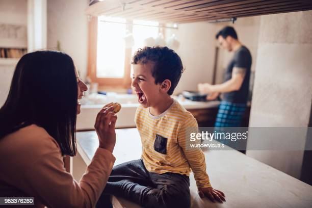 cheerful mother giving little son cookie in the morning - 4 5 anni foto e immagini stock