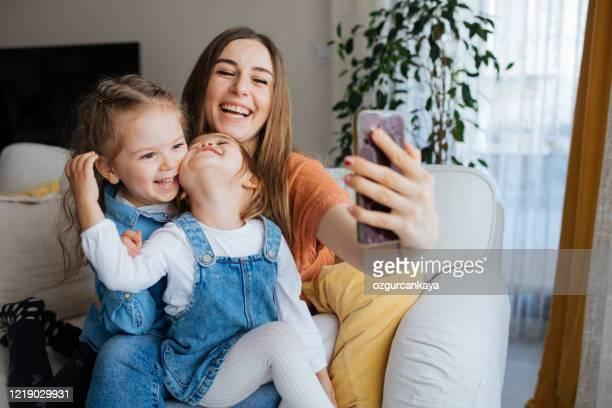 fröhliche mutter hält smartphone machen selfie mit töchtern - mother daughter webcam stock-fotos und bilder