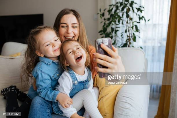 cheerful mother holding smartphone making selfie with daughters - middle east stock pictures, royalty-free photos & images