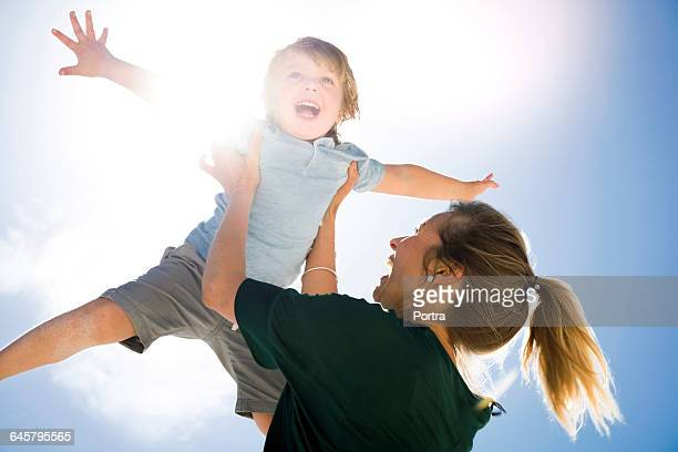 Cheerful mother lifting son against sky