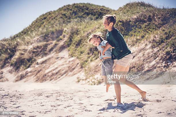 Cheerful mother lifting son at beach