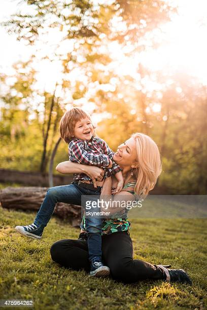 Cheerful mother playing in nature with her son at sunset.