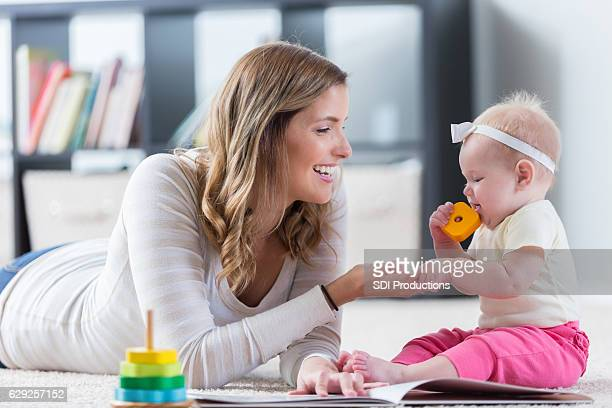Cheerful mother plays with baby girl