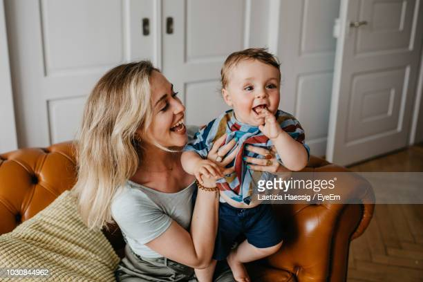 cheerful mother with son at home - junge familie stock-fotos und bilder