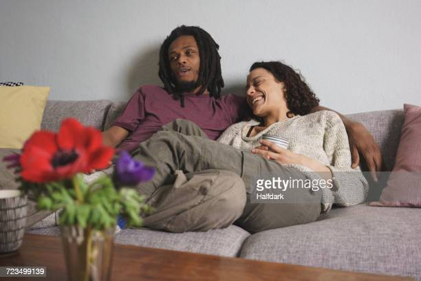 Cheerful multi-ethnic couple relaxing on sofa at home