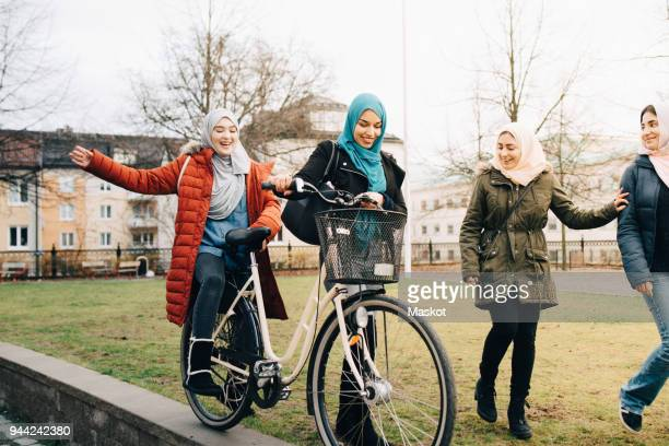 cheerful multi-ethnic female friends walking with bicycle on grass in city - modest clothing stock pictures, royalty-free photos & images