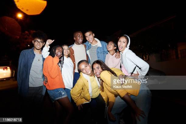 cheerful multi-ethnic friends on street at night - generation z stock-fotos und bilder