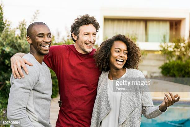 Cheerful multi-ethnic friends standing in yard