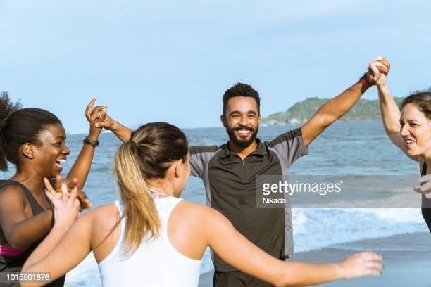 fröhliche multiethnischen sportliche Freunde am Strand im sonnigen Tag