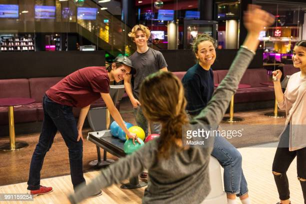 cheerful multi-ethnic teenagers enjoying at bowling alley - ボーリング場 ストックフォトと画像