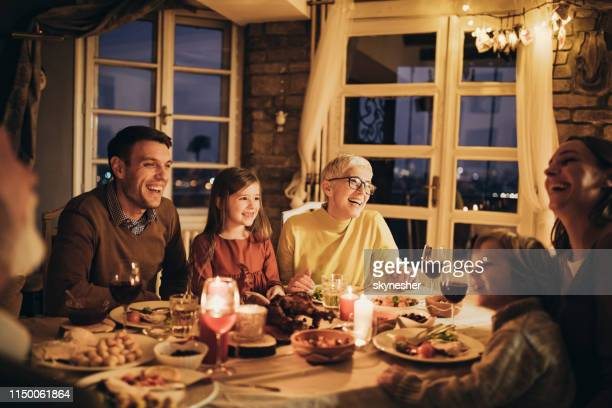cheerful multi-generation family talking during dinner at home. - evening meal stock pictures, royalty-free photos & images