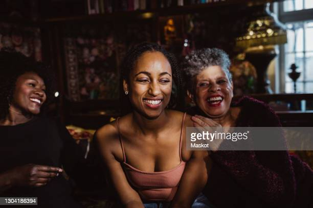 cheerful multi-generational females sitting in bedroom at apartment - women's issues stock pictures, royalty-free photos & images