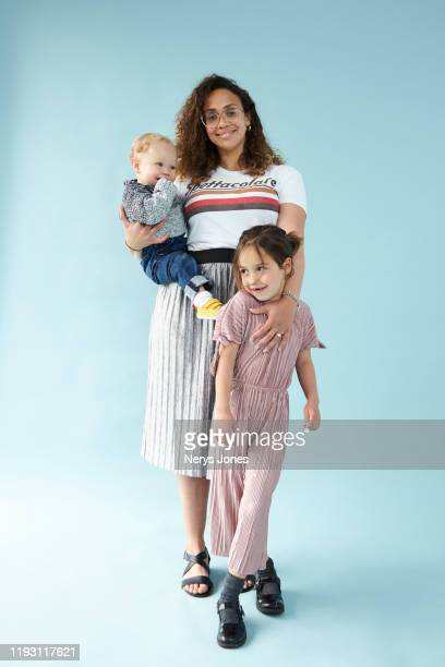 cheerful mum and her children against pale blue background - nerys jones stock photos and pictures