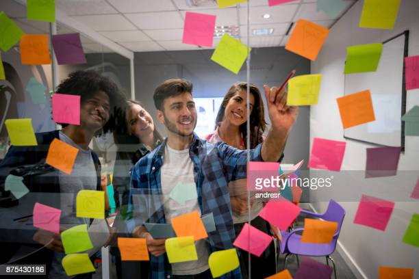 Cheerful muti ethnic group at the board room writing ideas on adhesive notes working together