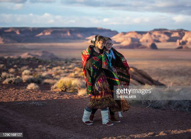 cheerful navajo sisters walking on a small path in monument valley - usa - navajo culture stock pictures, royalty-free photos & images