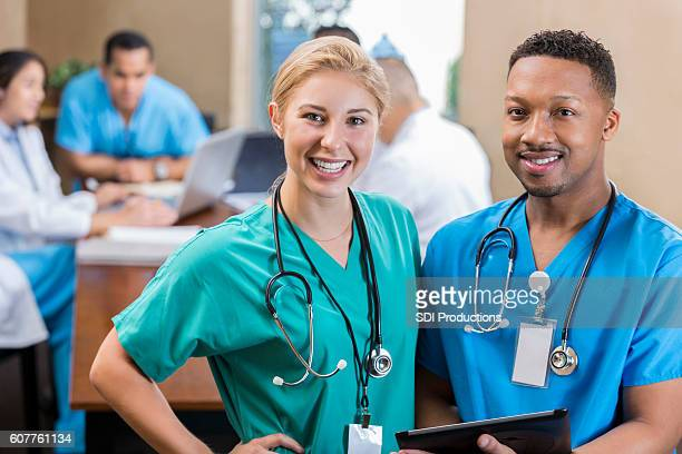 Cheerful nurse friends at hospital staff meeting