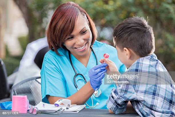 Cheerful nurse gives young boy lollipop after medical exam