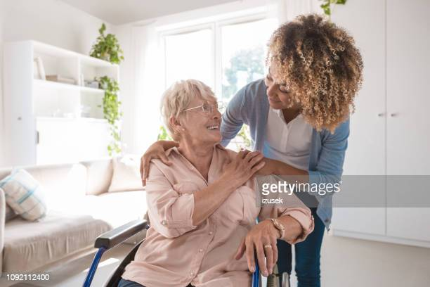 cheerful nurse taking care of eldery lady - a helping hand stock pictures, royalty-free photos & images