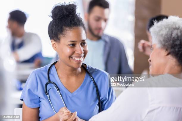 Cheerful nurse talking with senior female patient