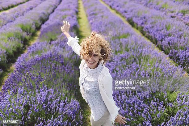 cheerful of woman dancing on lavender field - bortes stockfoto's en -beelden