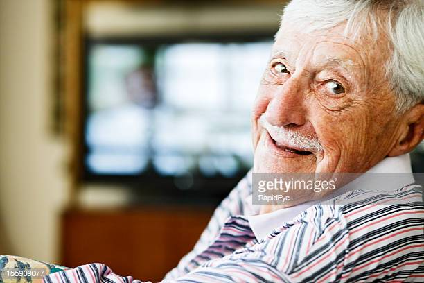 Cheerful old man looks over shoulder from watching television